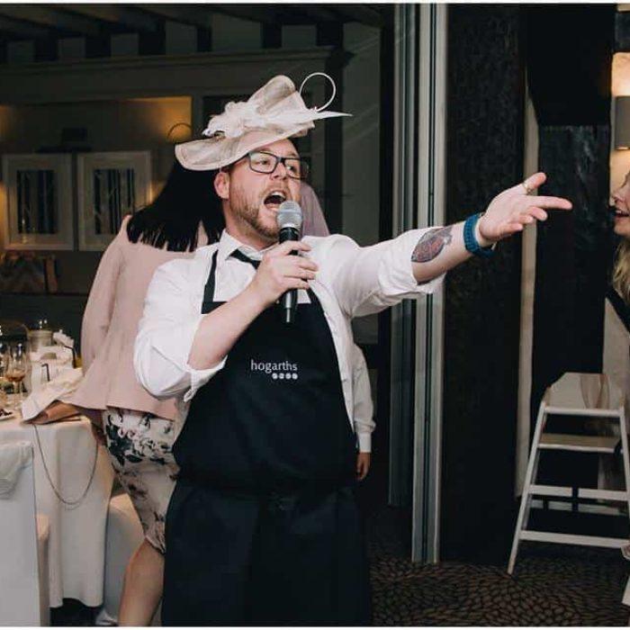 singing waiter wearing a hat